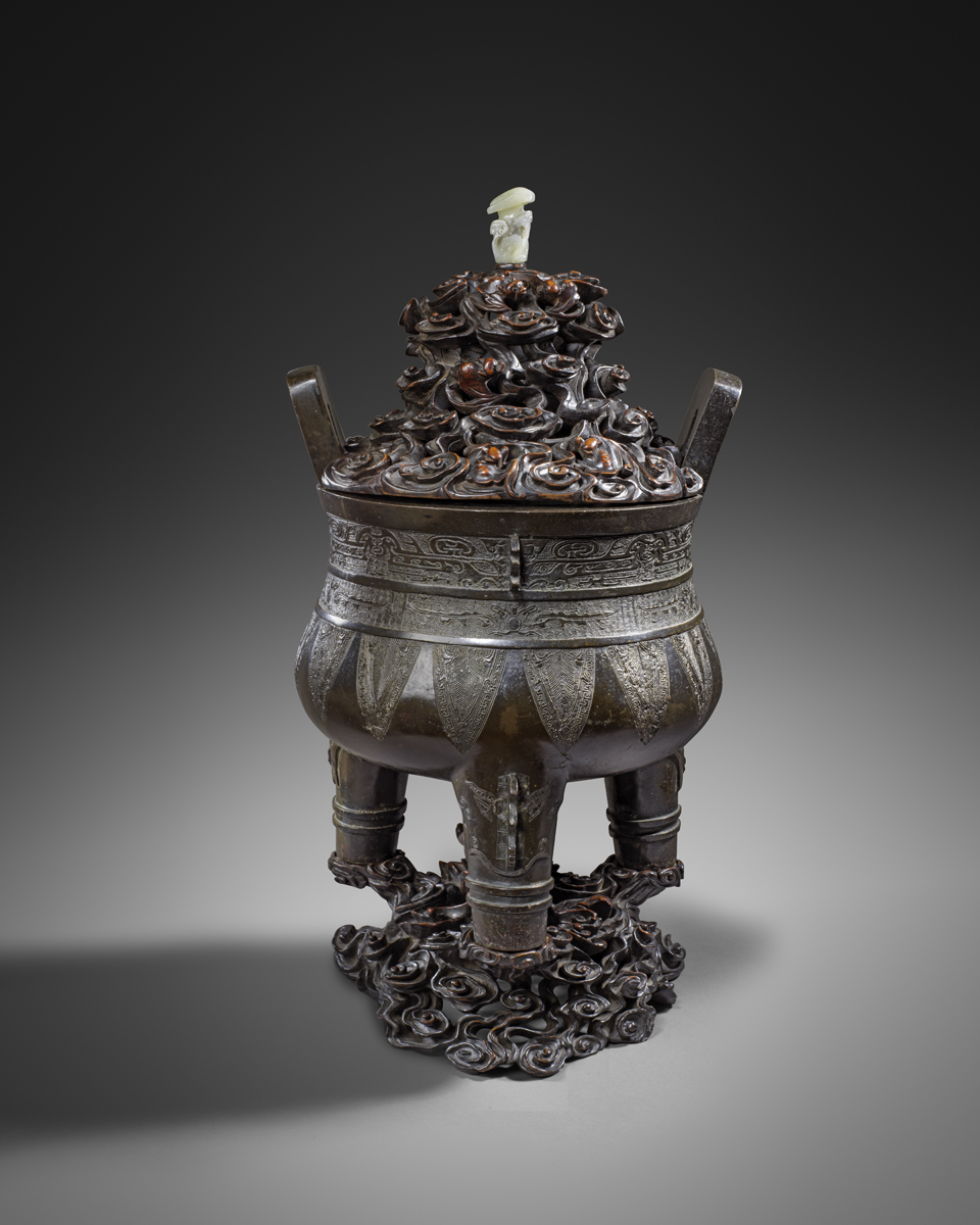 Dimensions: the censer 30 cm. diam.; 41.5 cm. high Provenance: - A private Asian Collection The censer has a deep rounded bowl rising from three conical legs to a flat rim and two upright bracket handles. It is decorated with a band of 'taotie' masks with central flanges; followed by a band of archaistic dragons and downward blades. The legs are cast with vertical flanges above two raised bands and cold worked with 'taotie' masks. The bronze has a deep dark brown patina. The censer is fitted with an elaborate wood stand carved with a dragon emerging from clouds, and a cover with further clouds and bats. The dating of the current censer is consistent with the thermoluminescence test, with two samples taken from the core material inside the legs, Certificate Number C110j84.
