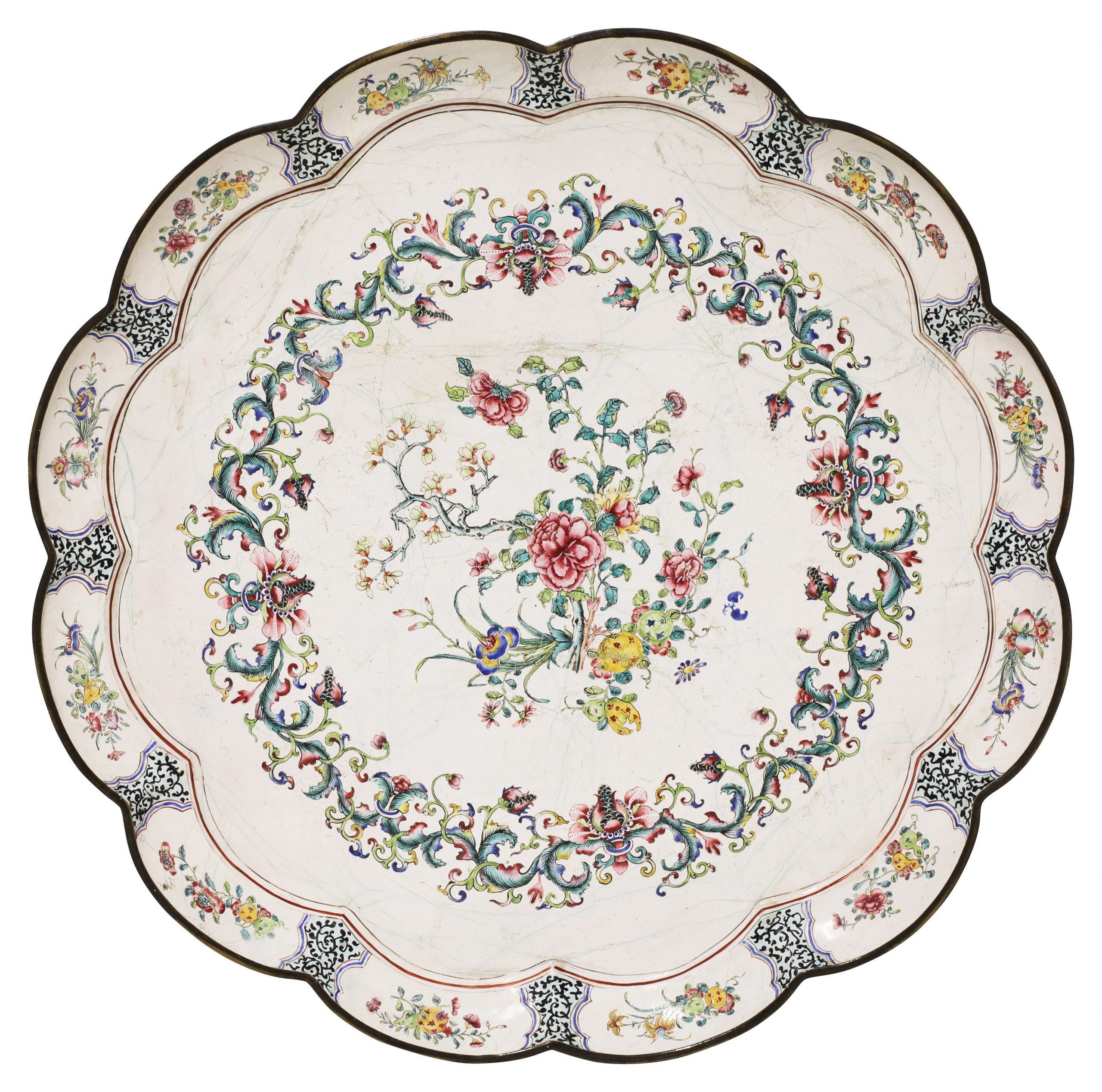 Of lobed form, the centre painted with a bouquet of blossoming peony, magnolia and finger citrons, enclosed within a border of scrolling foliage, the sides with further flower and fruit sprays in shaped panels between stylised block foliate scrolls, the reverse similarly decorated, 62.7cm diameter Provenance: Christie's, London, 14 May 2019, lot 111. 清十八世纪 铜胎画珐琅花果纹花口大盘