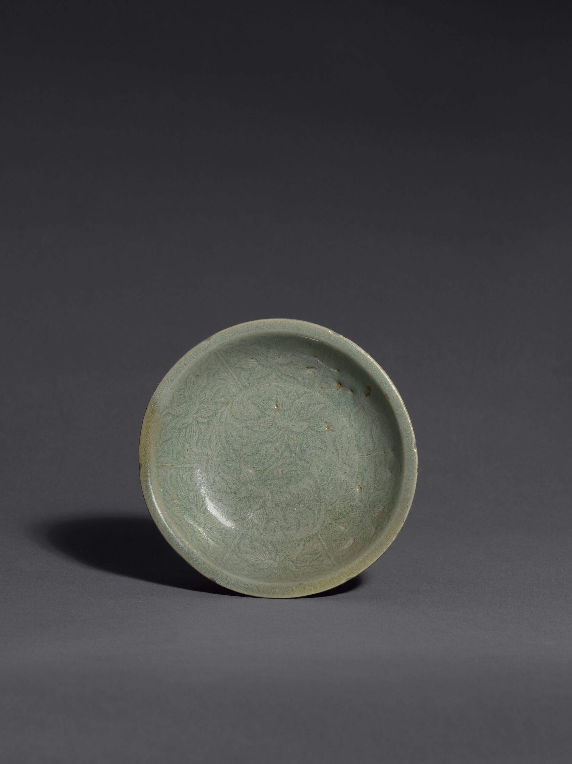 A CARVED KOREAN CELADON LOTUS-PATTERN FLOWER-SHAPED DISH Goryeo dynasty (918-1392), 12th century Diameter: 11.8 cm, 4⅝ inches 高麗 十二世紀 青瓷刻蓮花紋碟 直徑11.8釐米