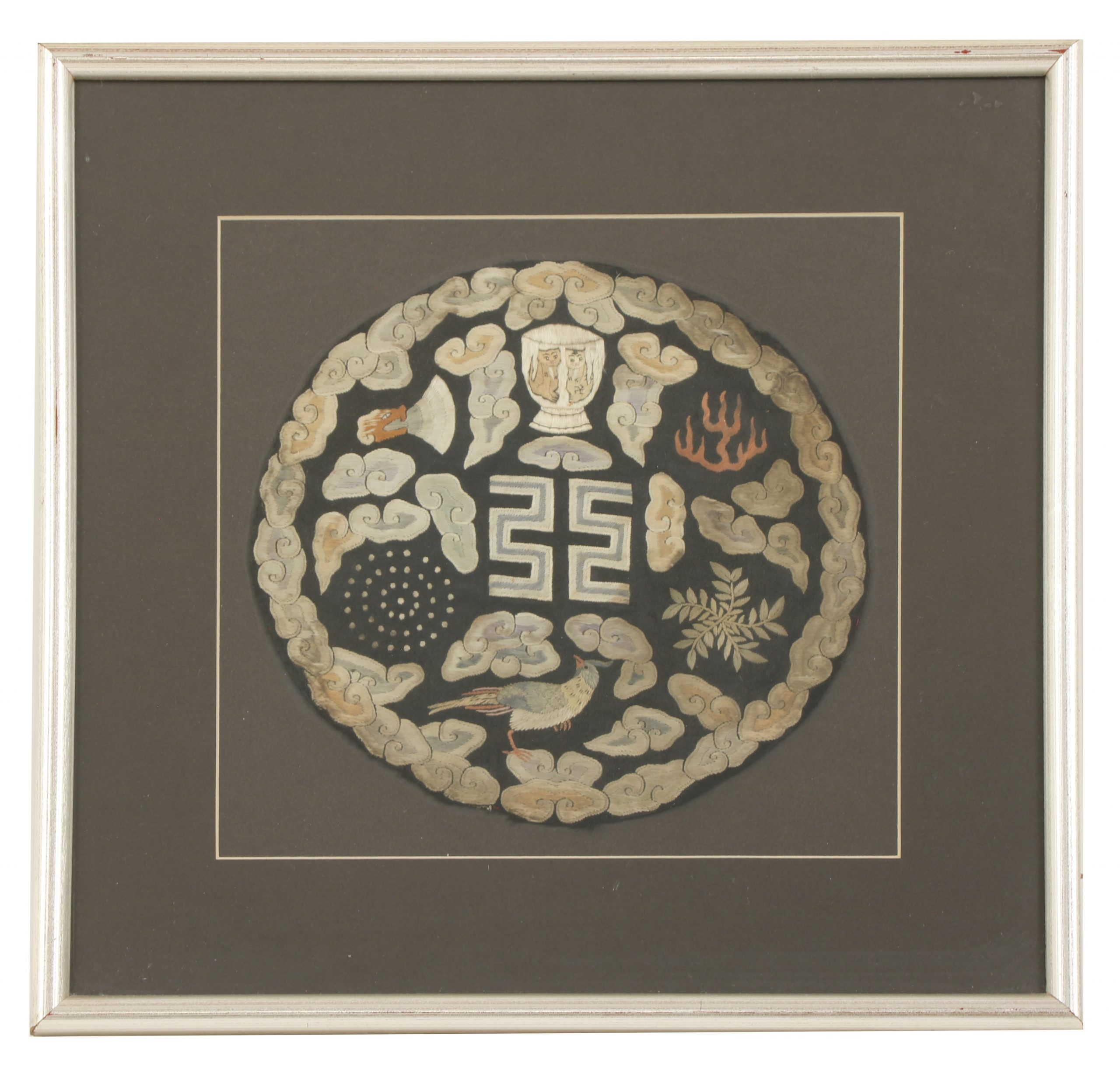 After 1911, of 'Yuan Shikai roundels', each embroidered with the symbols of sovereignty, including the fu surrounded by libation cups, fire, a constellation, a dragon, a mountain, a pheasant, an axe or a water weed, amongst clouds against a black satin ground, 20 to 21cm diameter, framed and glazed (4) After he became the first President of the Chinese Republic in 1912, Yuan Shikai had a desire to emulate the old Imperial ranking system. These roundels were made to be worn by officials during the traditional seasonal sacrifices he reinstated. The lower the status of the official, the fewer roundels on his robe, and the fewer traditional symbols of Imperial authority included in the roundel, with twelve being the highest number for roundels and symbols. For further examples of roundels of this type, displaying a varying numbers of symbols, see B Jackson and D Hughes, 'Ladder to the Clouds', Berkeley, 1999, pp. 286-9. Provenance: Two purchased from Christie's, New York, 19 Mar 2008, Lot 81. 民国 补子 一组四件