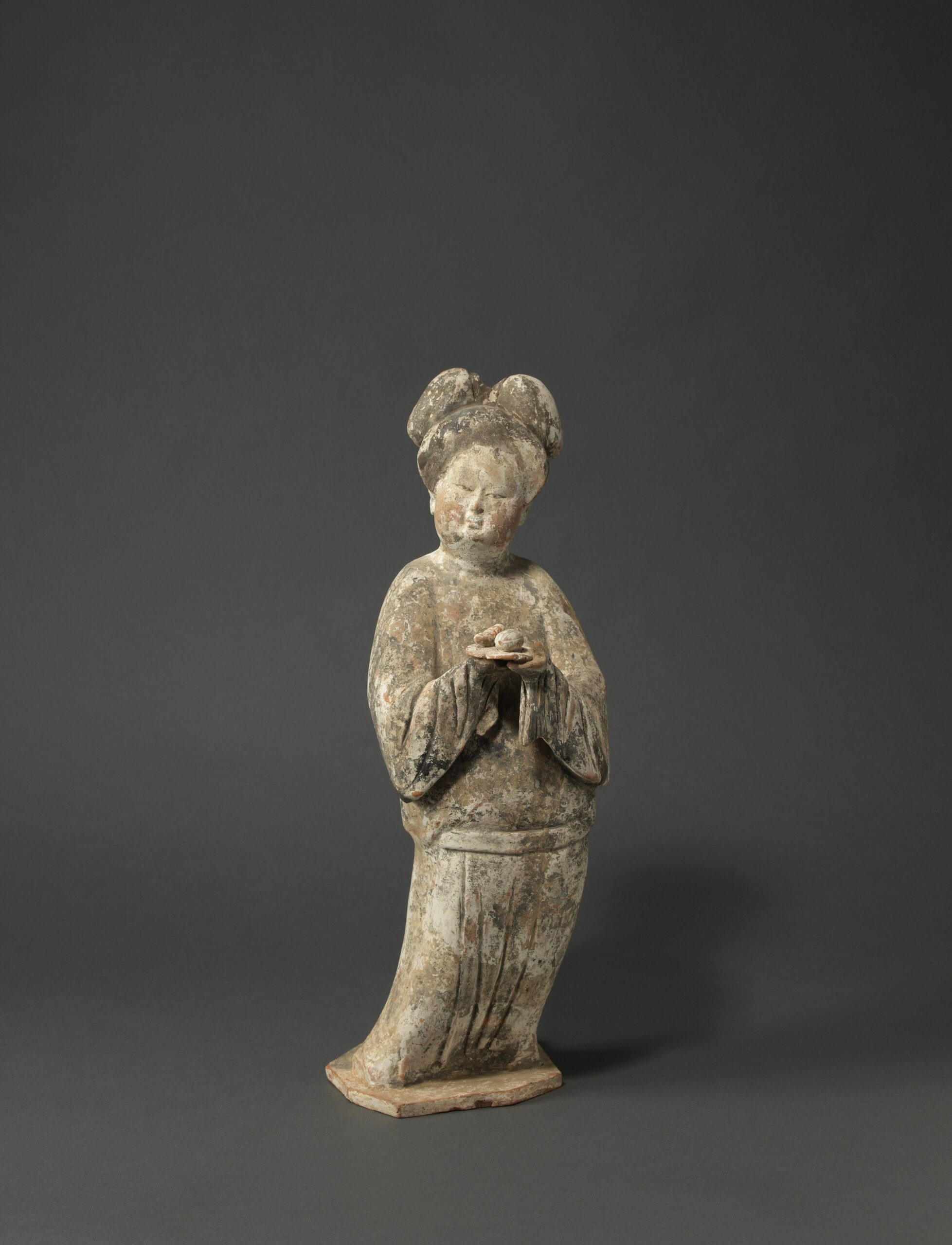 A PAINTED POTTERY FIGURE OF A COURT LADY HOLDING A DISH OF FRUIT Tang dynasty (618-906), first half 8th century Height: 46 cm, 18 inches 唐 彩繪陶捧盤仕女俑 高46釐米