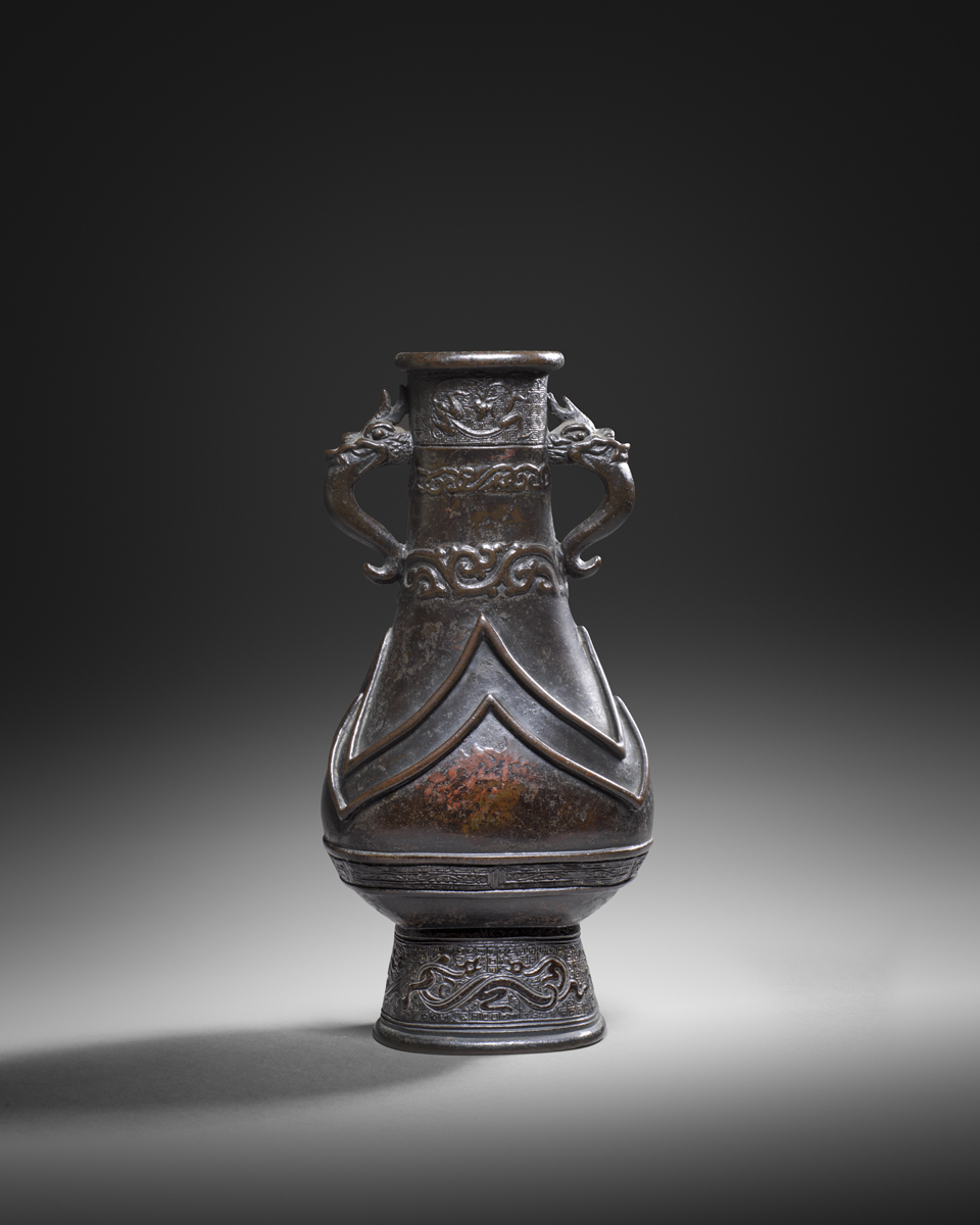 Dimensions: 27cm high Provenance: An English private collection, acquired in the 1990s and 2000s The vase of archaistic 'hu' form, the neck finely cast with horizontal sections of archaistic decoration against a 'leiwen' ground and bands of intertwined scrolls, flanked by a pair of dragons with long, wide tongues. The bulbous body divided into separate sections by two bands in high relief. The high foot with intertwined 'kui' dragons on a 'leiwen' diaper ground. The vase has a rich, dark patina with traces of red lacquer.