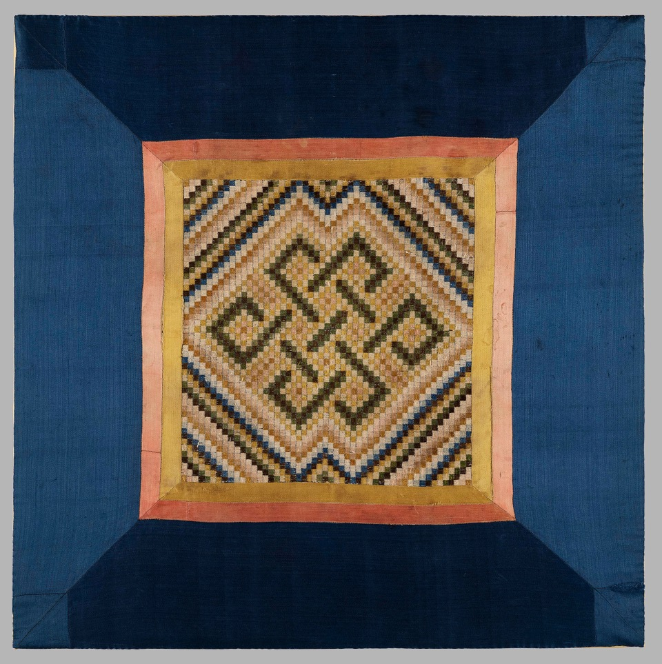A square silk meditation panel, composed of 51 by 51 small embroidered squares, forming a design of an Endless Knot, symbolising the cycle of birth, death and rebirth. Set within a wide blue silk border.