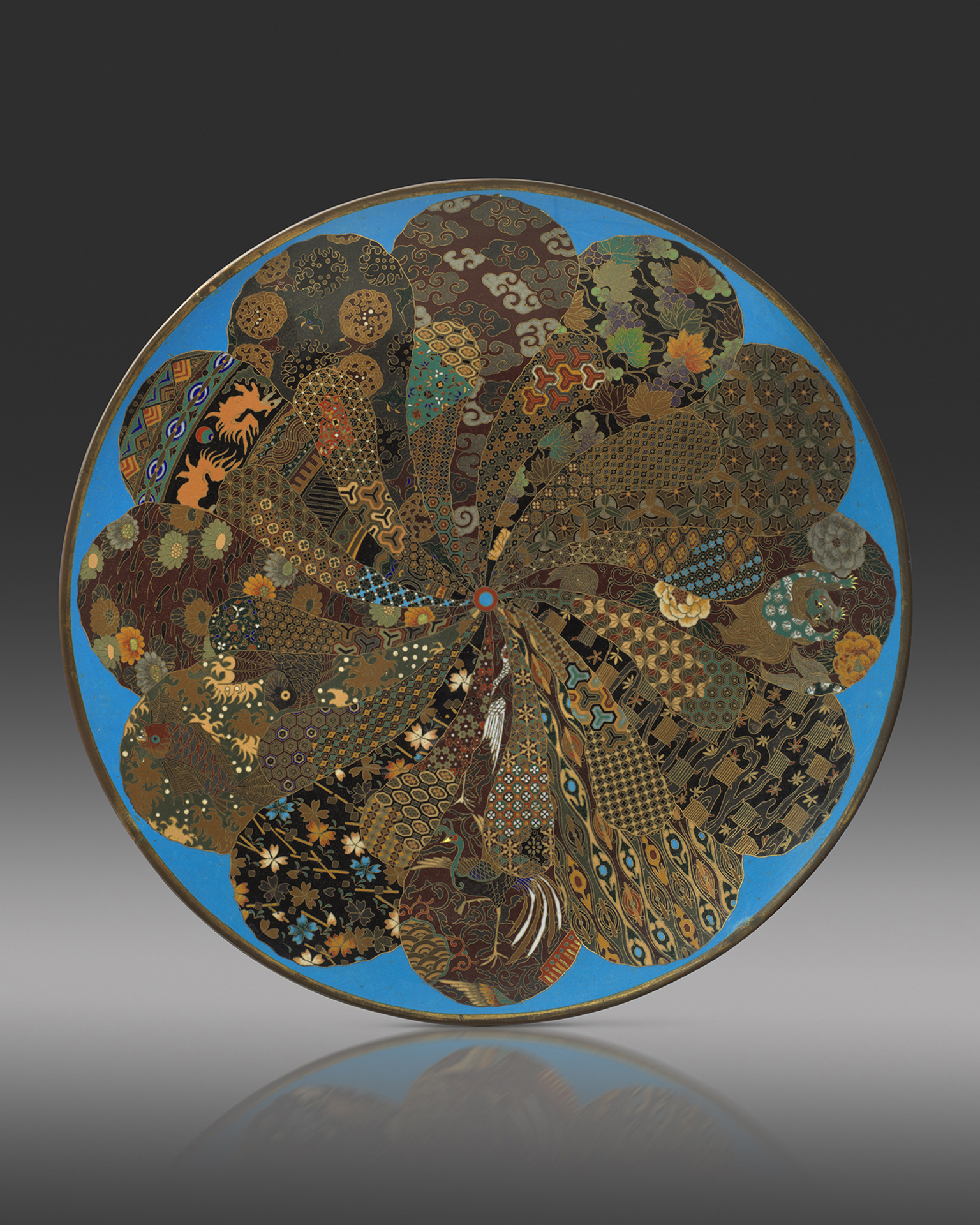 A cloisonne enamel dish worked in gilt wire with a radiating petal-like design of natural and geometric motifs, 45.5cm, Meiji Period Circa 1890