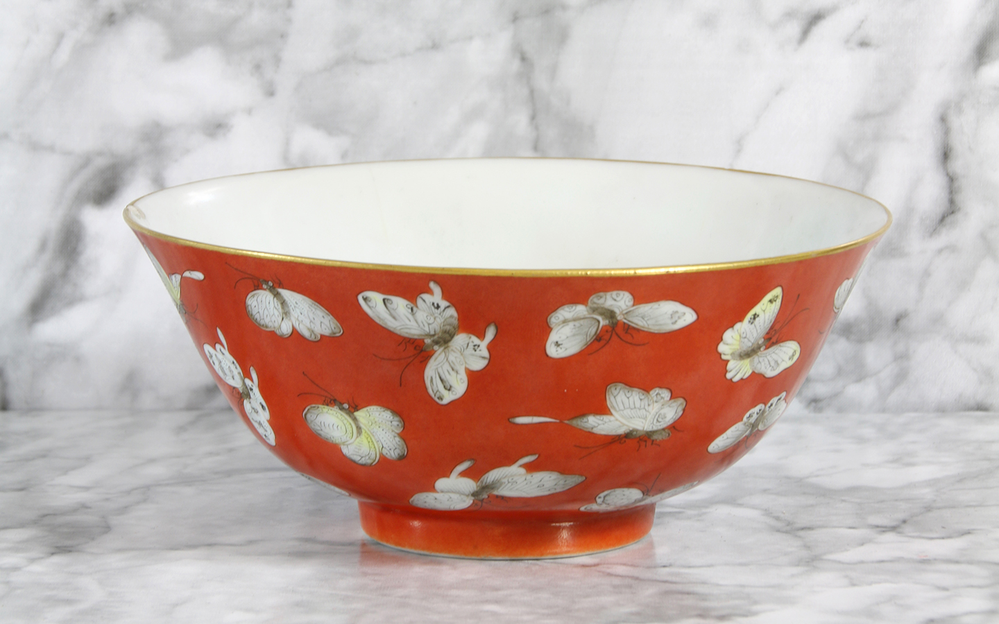 Finely potted, the rounded sides with slightly everted rim, painted with various butterflies, all reserved on a rich coral-red ground, the interior glazed white, the base with a four-character mark Shende Tang zhi ('Made for the Hall of Prudent Virtue') in iron red,
