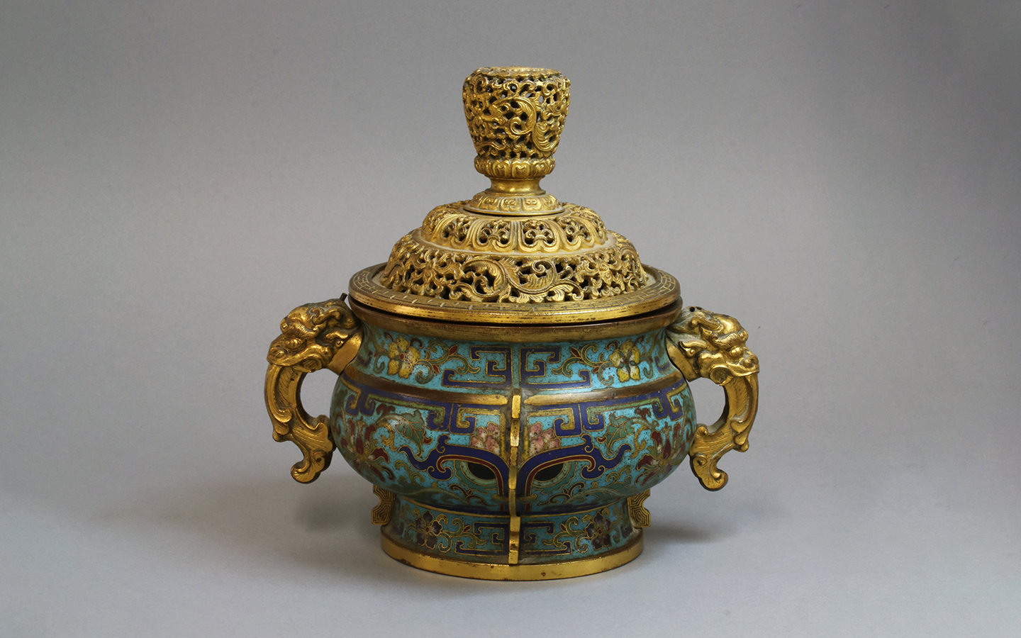 The compressed globular body rising from a short spreading gilt foot to a short neck with everted gilt rim, set at the shoulder with a pair of stylised dragon handles, brightly decorated around the exterior with taotie mask surrounded by leafy scrolling lotus reserved on a turquoise ground divided by vertical flanges with key frets, the gilt pierced domed cover finely decorated with scrolling lotus and lotus petals surmounted by a bud-shaped finial similarly decorated, 
