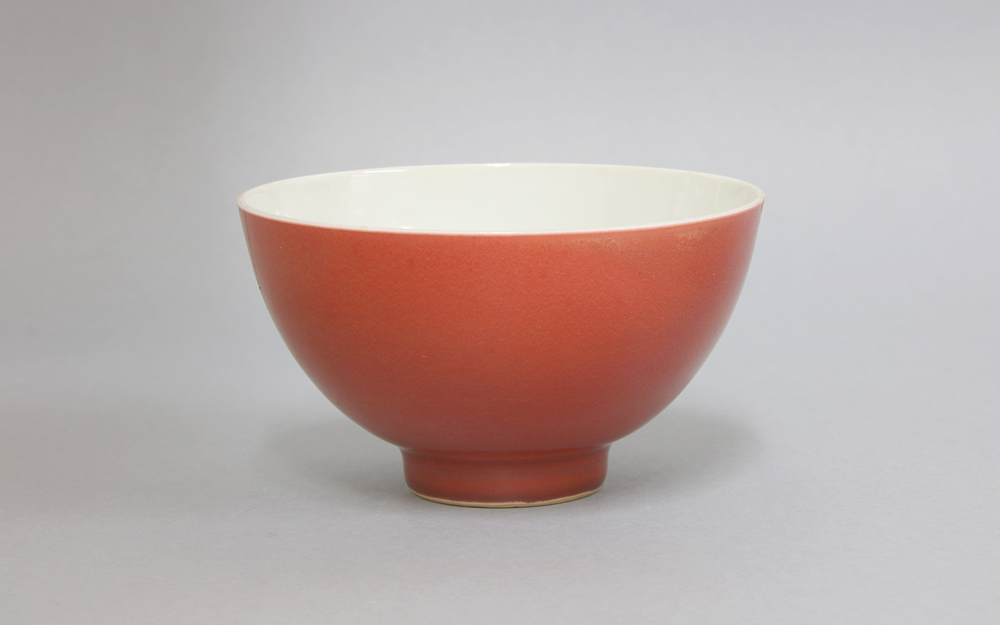 Well potted with deep flaring sides supported on a short circular foot, covered on the exterior with a liver-red glaze, six-character Yongzheng mark in blue to base,