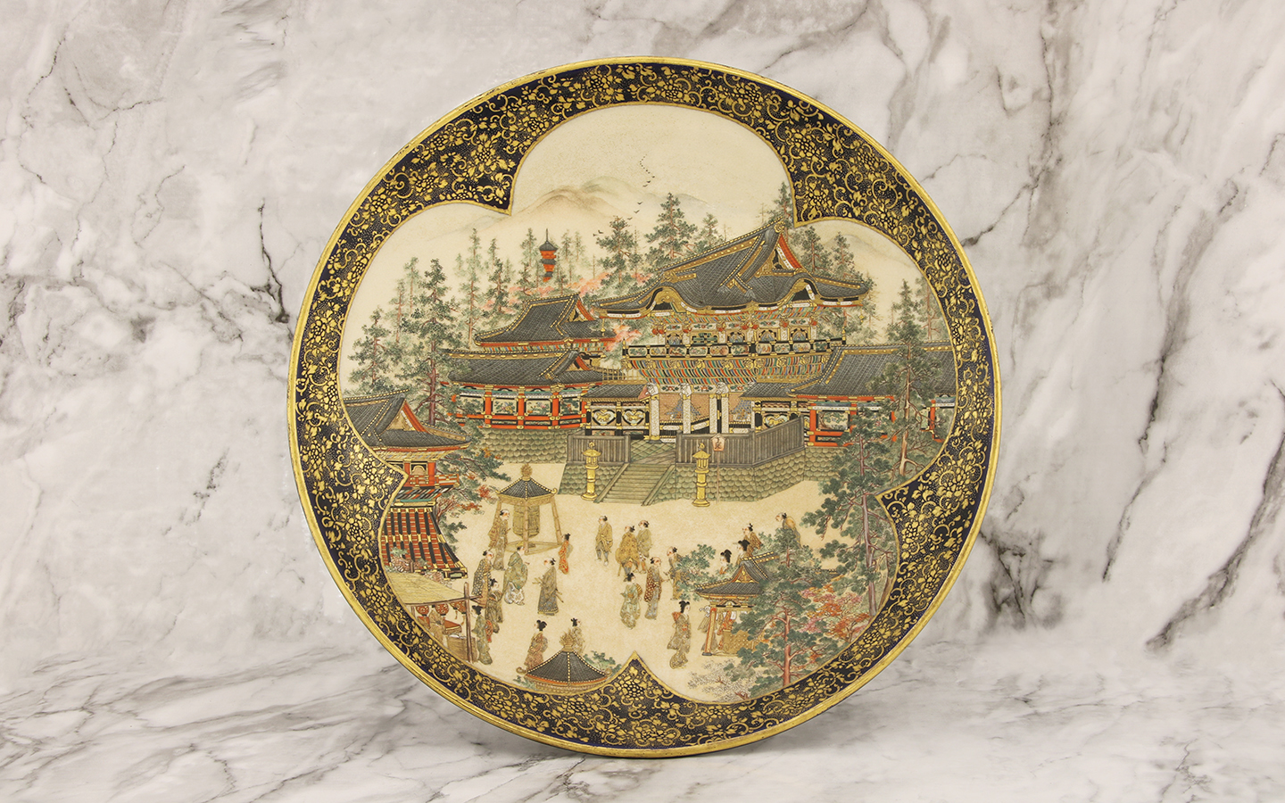 Of circular form, painted in a prunus shaped panel with figures in the yard of Kiyomizu-dera amongst maple and pine trees in Kyoto, surrounded by scrolling flowers in gilt against a midnight blue ground, Kinkozan mark to base,