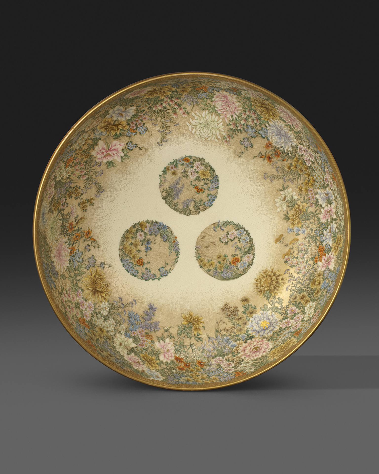 A large earthenware bowl, finely painted and gilt on both interior and exterior with numerous flowers. Signed and impressed Kinkozan zo, Meiji Period Circa 1900, 28.2cm