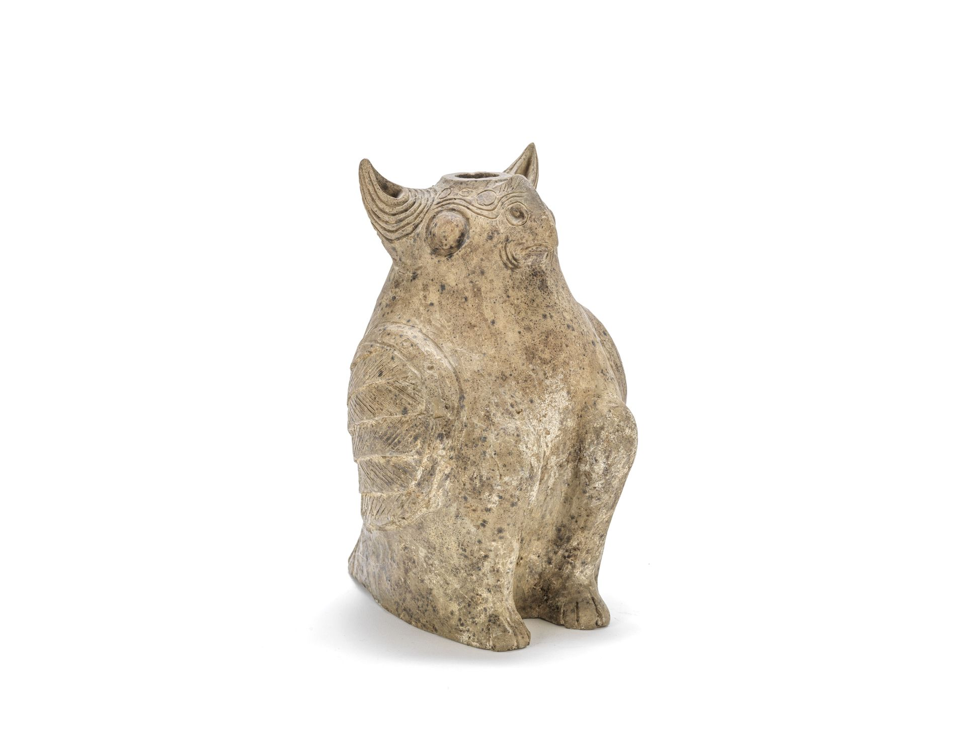 A large and rare grey pottery model of a long-eared owl, Western Han Dynasty. Modelled as a plump seated owl with long pricked ears and a crest rising from the short beak, with incised linear designs, a circular aperture to the top of the head, the wings folded back neatly against the body. 28.5cm. (11.1/4in) high. £3,000-5,000