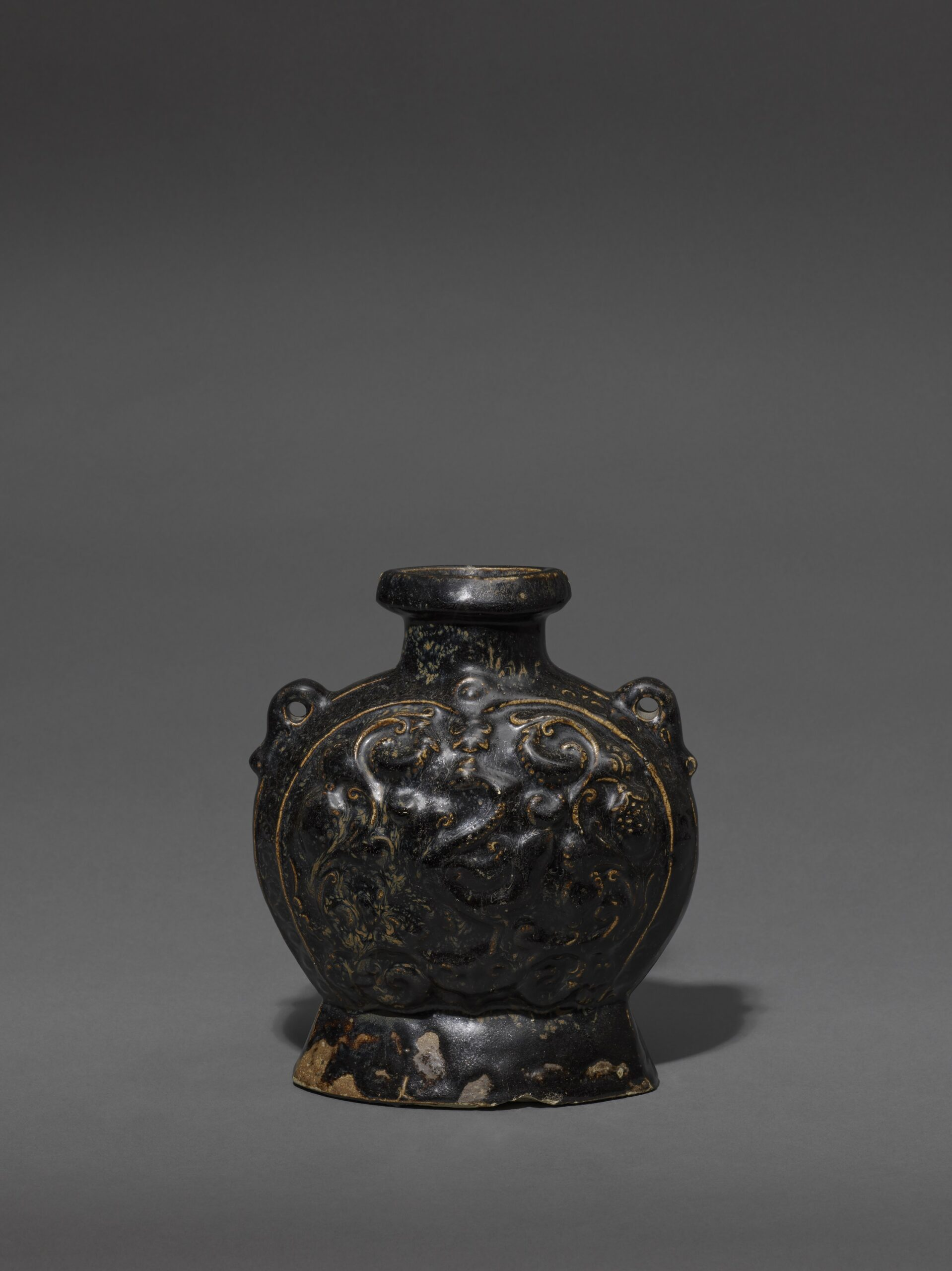 A BLACK-GLAZED STONEWARE PHOENIX-PATTERN PILGRIM FLASK Sui dynasty (581-618) or early Tang dynasty (618-906) Height: 23.2 cm, 9 ⅛ inches 隋或唐 黑釉瓷葡萄鳳紋扁壺 高23.2釐米