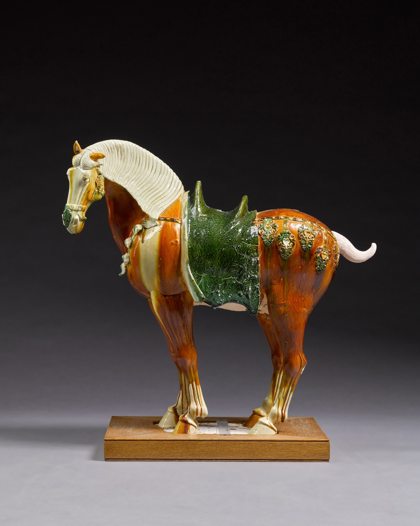 A magnificent large sancai-glazed figure of a caparisoned Fereghan horse, Tang dynasty