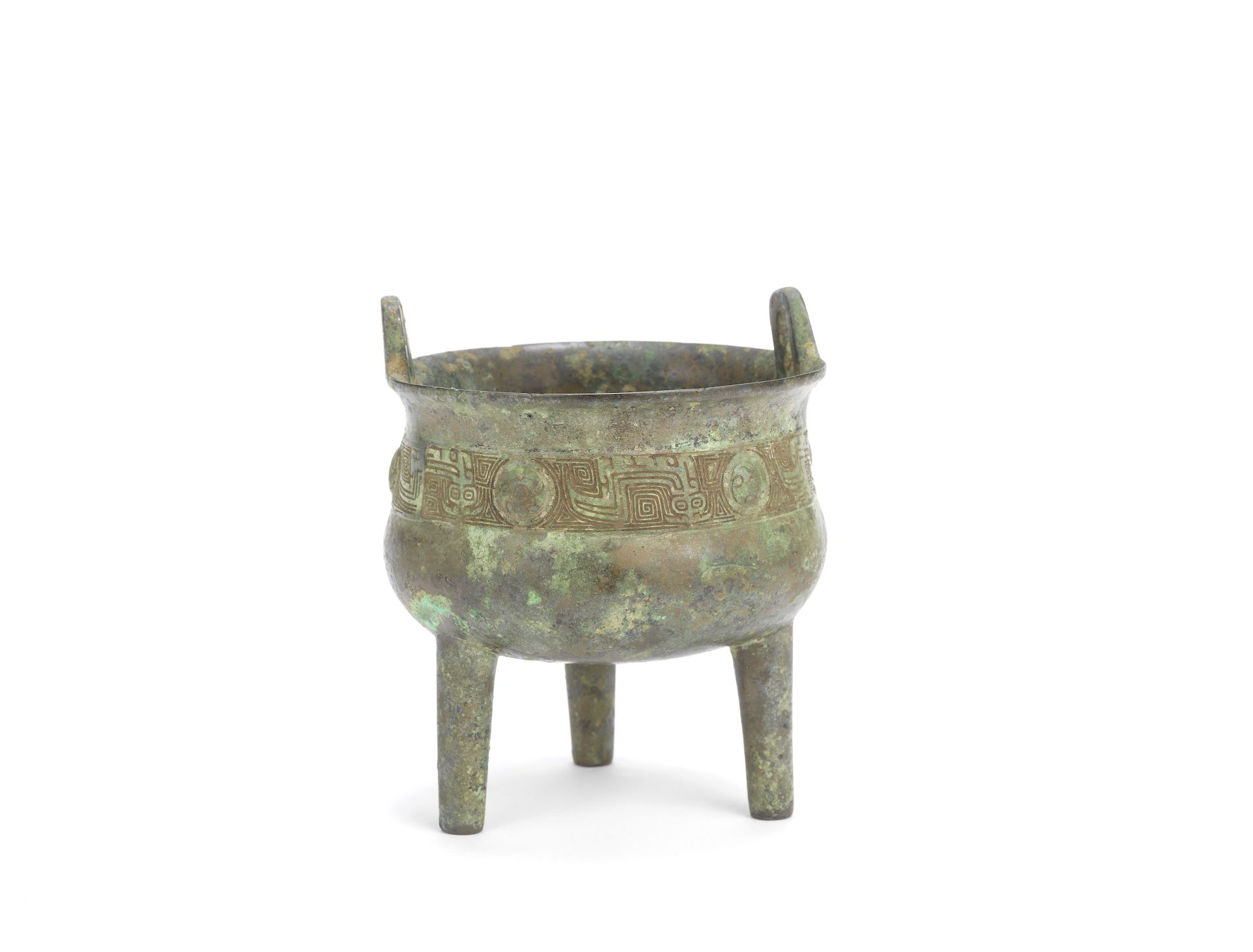 An archaic bronze ritual tripod vessel, ding, Shang/Western Zhou Dynasty. The globular body with upright loop handles, supported by three slender, tubular legs, with incised stylised dragon band and raised bosses below the flaring rim, fitted wood stand, the interior with four small moulded marks, the patina of a mottled greyish-green hue. 16.5cm (6 1/5in) high (3). £3,000-5,000