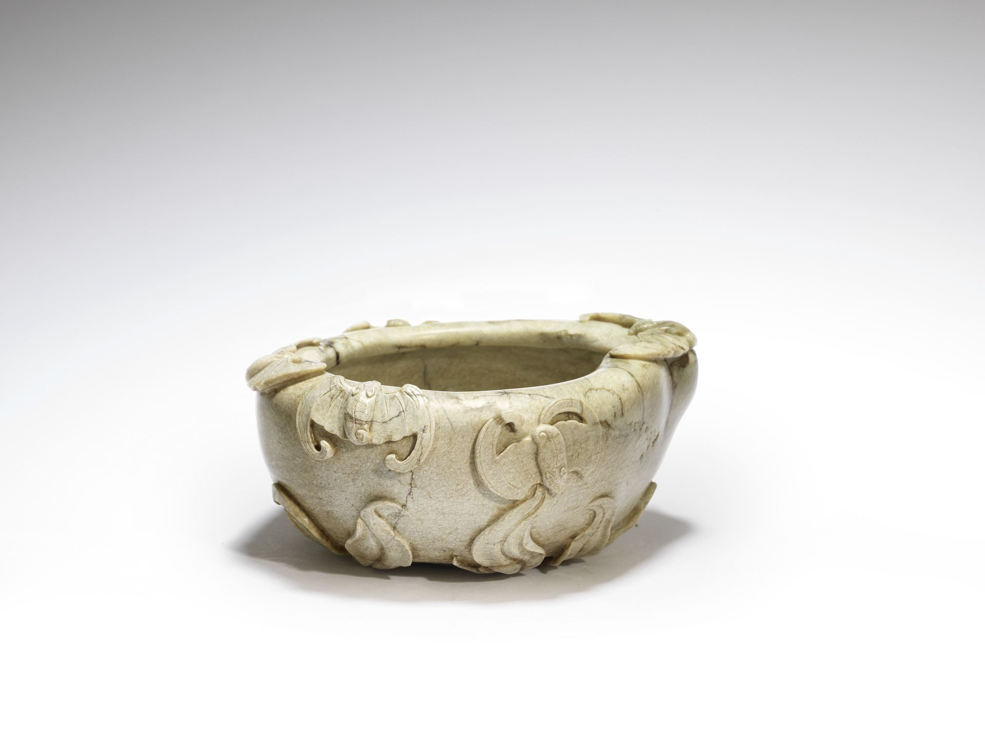 A chicken bone jade 'peach' washer, 18th century. Finely carved with five bats around the rim, and with gnarled, leafy branches to the base and rising up the sides, the stone of an opaque creamy beige-flecked tone, box. 15.5cm (6.1/8in) wide. £7,000-9,000
