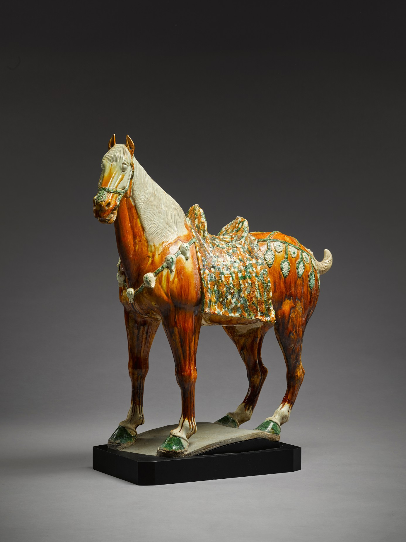 A large sancai-glazed figure of a caparisoned horse, Tang dynasty