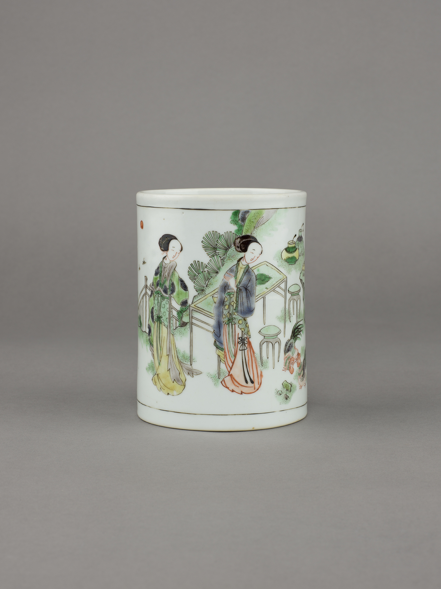 no. 18 - Chinese porcelain famille verte, wucai brush pot, bitong, with two panels; one with two elegant ladies standing beside a pair of chickens, next to a table and stools in a fenced landscape scene. 5 ¼ inches, 13.4 cm high; 4 inches, 10.2 cm diameter. Kangxi, 1662-1722.