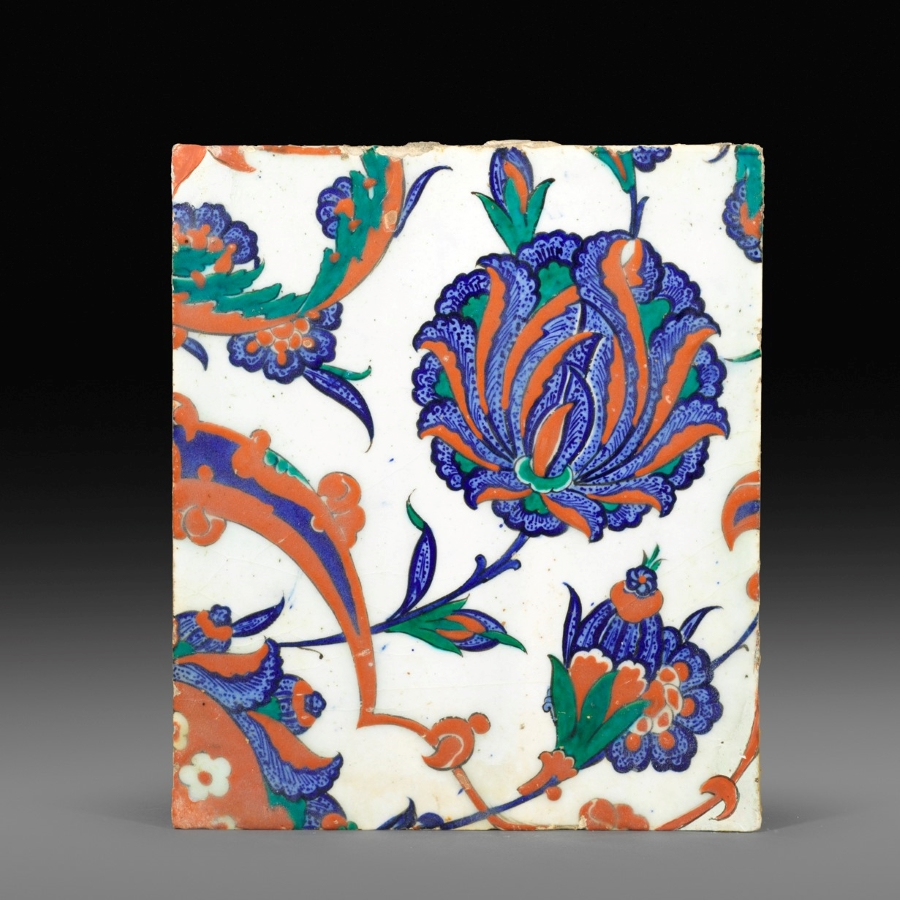 Iznik pottery tile, Turkey, 1570-80, Painted in underglaze blue, viridian green and bole red on a white ground, with large composite flowers and arabesques forming a spiral, 25.6 by 22 cm