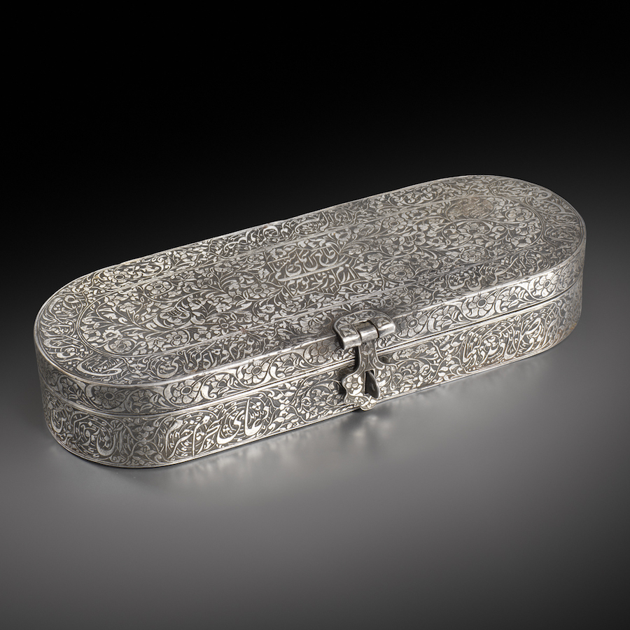 A Qajar steel pen-box inscribed to Gawhar Khanum, daughter of Fath 'Ali Shah (r. 1797-1834) Persia, dated A.H. 1231 / 1815-16 A.D. Of cartouche form with twin hinges at the back and a floral clasp at the front, engraved with a dense design of flowering plants, enclosing on the top a cusped panel with the name and date, cusp-ended cartouches of nastal'iq around the borders and encircling the sides, the interior with an inner band of further inscriptions interrupted by four small ink-wells with hinged lids around a central vacant cartouche-shaped recess. 25.2 by 9 by 4.2 cm.