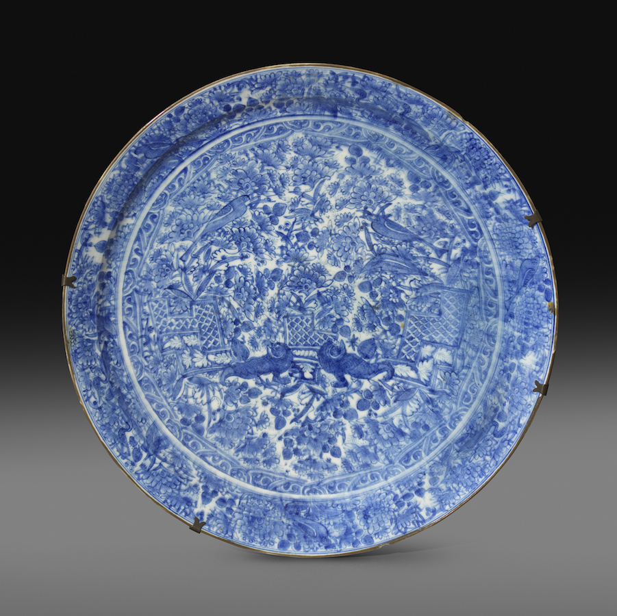 A large Safavid blue and white pottery dish, Persia, late seventeenth century, Painted in cobalt blue under a transparent glaze, the field depicts a pair of adorned guardian lions supporting a trellis platform. 53.8 cm. diameter; 10.6 cm. height