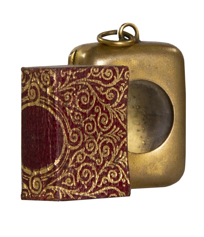 Miniature printed Qur'an, in Arabic, 27 by 19 mm. (32 by 25 mm. with case); clean and crisp condition, housed in original gilt stamped limp morocco covers, in original brass case with magnifying glass.