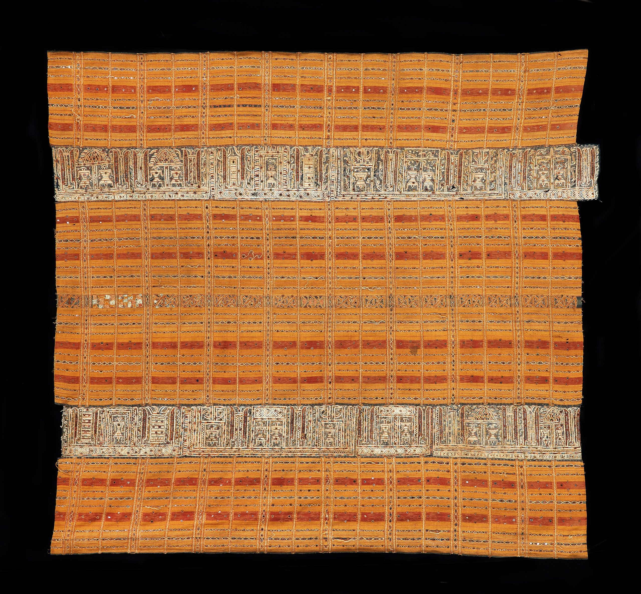 A ceremonial skirt, 'Tapis Kaca Kuning', handspun cotton, gold wrapped thread, silk embroidery, warp ikat, mica (muscovite) sequins, natural dyes, Paminggir people, Lampung, coastal Krui region, mid 19th century, 125cm x 120cm approx.