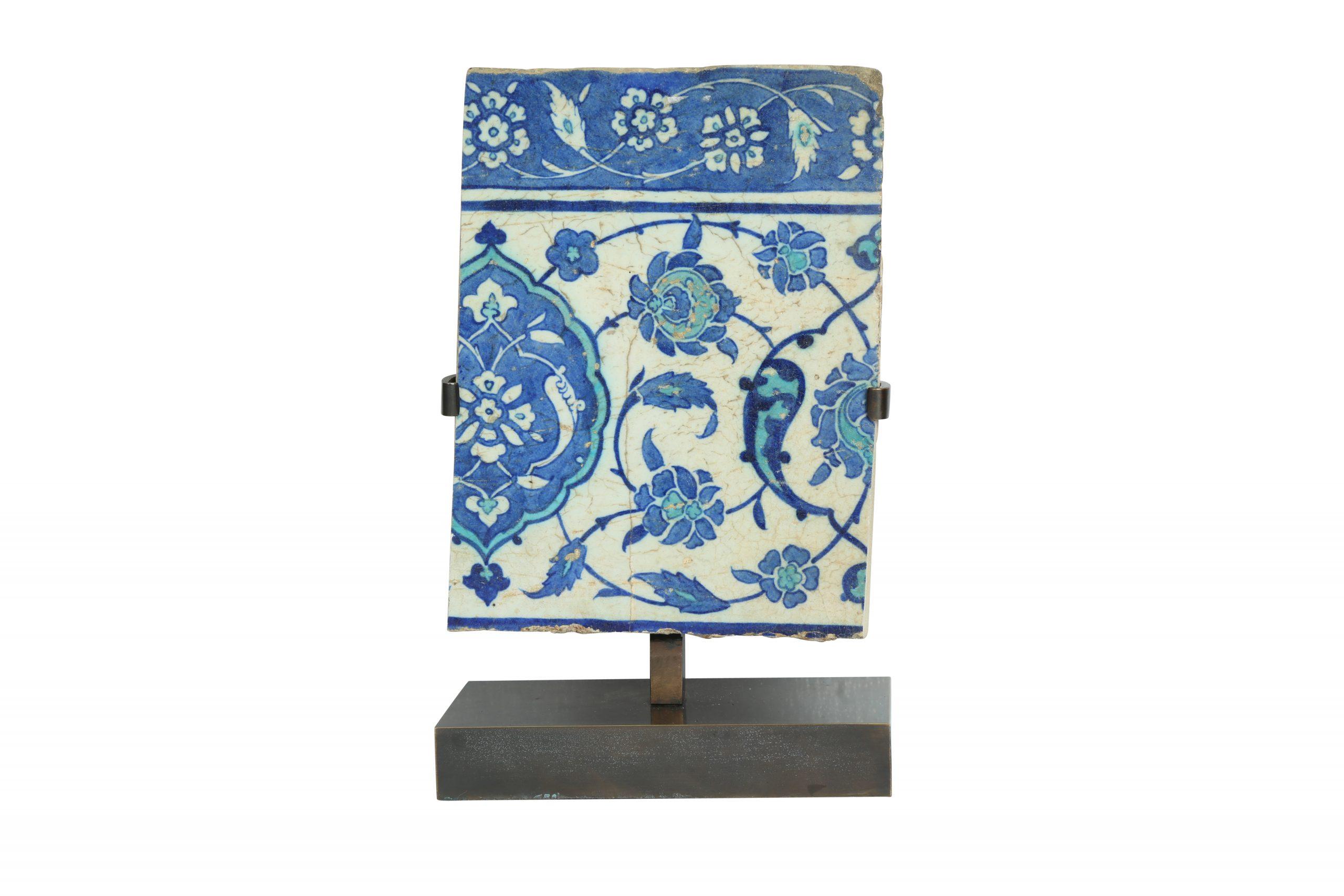 An iznik blue and turquoise pottery tile fragment. Ottoman Turkey, 16th century. Estimate £800 - £1,200