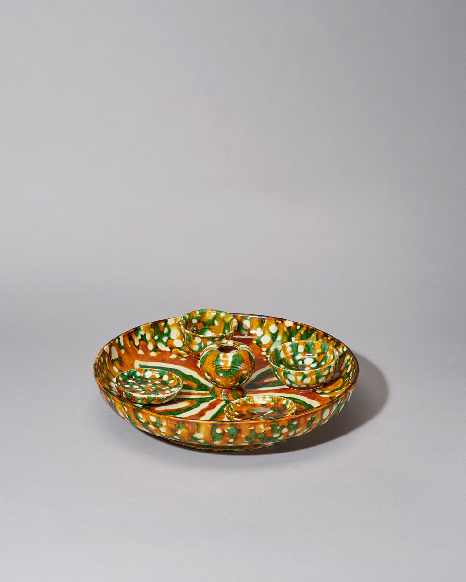 A Fine Sancai Plate with Cups and Pot, Tang Dynasty (618-907) The plate with shallow rounded sides rising to the everted rim, decorated with green, amber and cream spot glaze running over the exterior, with removable central pot, two smaller cups and two smaller plates. Diameter: 31cm