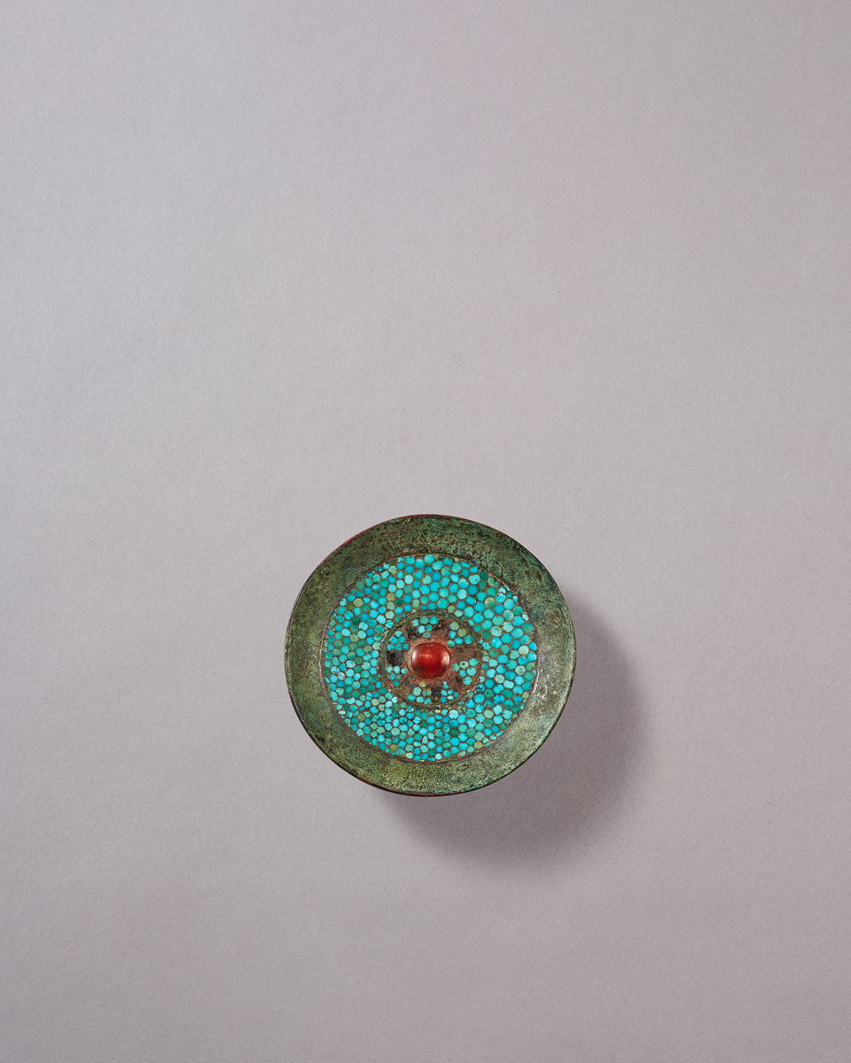 Bronze Buckle ornament with turquoise and agate inlay, Western Han Dynasty The shallow round plaque inlaid with a red agate bead in the centre, surrounding by small circular turquoise pieces, the reverse fitted with an angular pointed hook. Diameter: 9.3cm