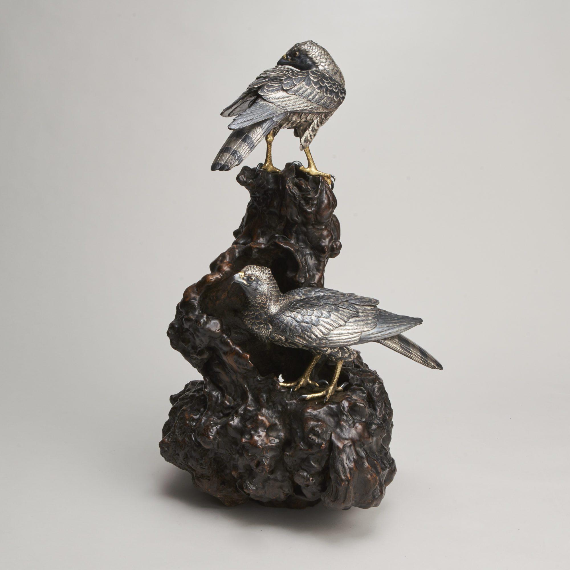 Okimono   A pair of Japanese Meiji Period multimetal hawks on a root wood base